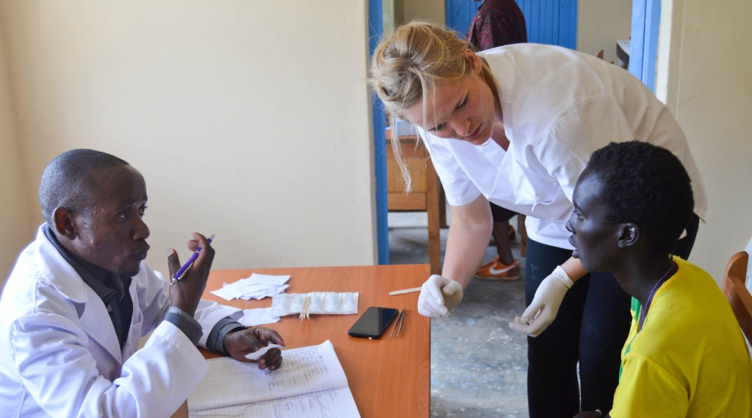 A recent graduate interning abroad assists a local doctor during a medical outreach in Kenya.